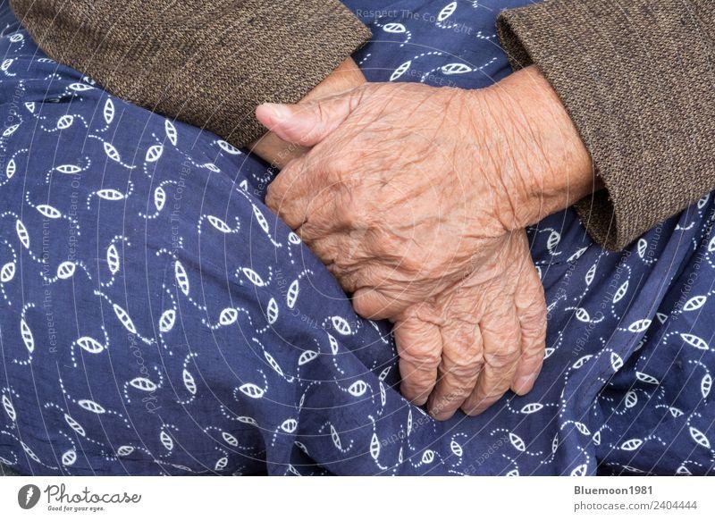 Ein Detail einer alten Frau, die ihren traditionellen Rock anlegt. Lifestyle Körper Haut Leben Ruhestand Mensch feminin Erwachsene Großmutter Hand Finger Stoff