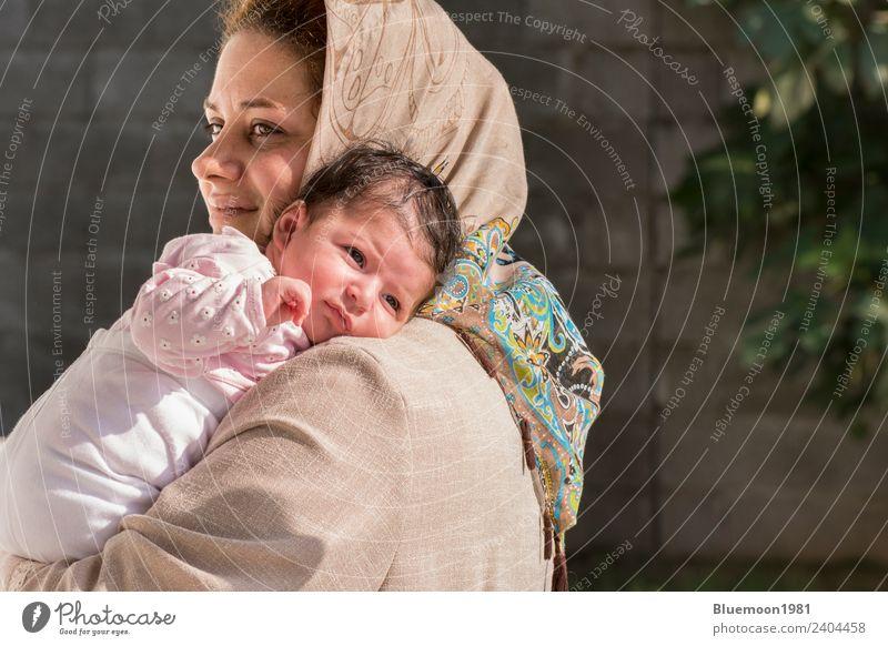 Muslimische Mutter, die ein kleines Neugeborenes im Freien betreut. Lifestyle schön Leben Erholung Kindererziehung Mensch feminin Baby Frau Erwachsene Eltern