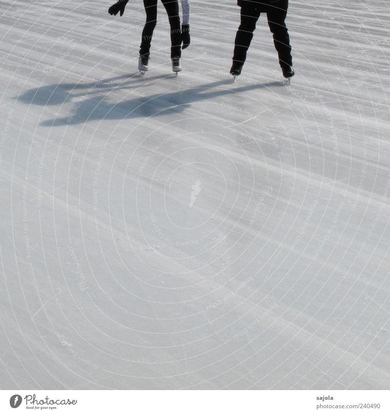 hilfe anbieten Wintersport Schlittschuhlaufen Mensch 2 fahren stehen weiß Eis Eisfläche Linie Schattenspiel Farbfoto Außenaufnahme Textfreiraum unten Tag
