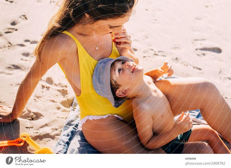 glückliche kaukasische Mutter und sein Sohn essen am Strand ein paar Wichser. Frucht Ernährung Glück Kind Kleinkind Frau Erwachsene Familie & Verwandtschaft