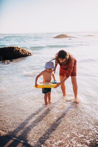 Mutter und Sohn beim Vergnügen mit dem aufblasbaren Ring am Strand Lifestyle Freude Glück Freizeit & Hobby Spielen Ferien & Urlaub & Reisen Sonne Meer Kind