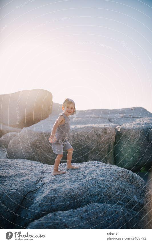 kleiner kaukasischer Junge klettert auf Felsen am Strand. Freude Glück Ferien & Urlaub & Reisen Sommer Sonne Klettern Bergsteigen Kind Kleinkind Kindheit Küste