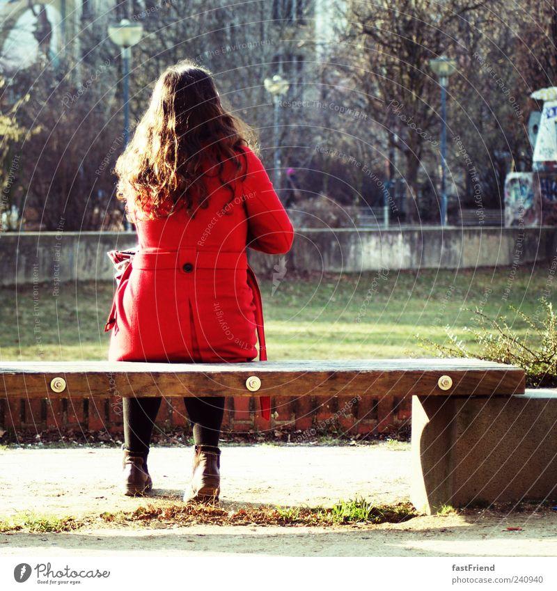 124 Sekunden Pause Frau Erwachsene Mensch Park Mantel schwarzhaarig Locken ruhig Einsamkeit Bank sitzen warten rot Holz Stein Farbfoto Außenaufnahme Tag