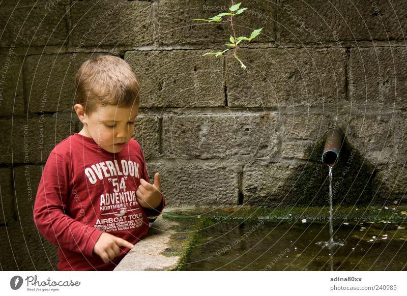 Neugier Junge beobachten Denken entdecken Erfahrung Farbfoto mehrfarbig Außenaufnahme Sonnenlicht Blick nach unten Brunnen Wasser zeigen Zeigefinger