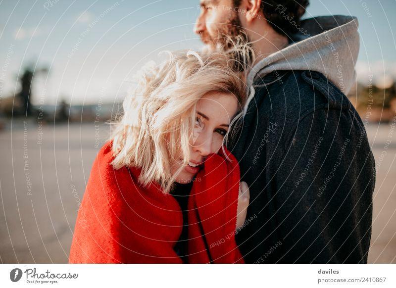 Blonde Frau, die ihren Freund umarmt. Lifestyle Freude Sonne Winter Erwachsene Mann Paar Mode blond Lächeln Liebe Umarmen Coolness Fröhlichkeit Zusammensein rot