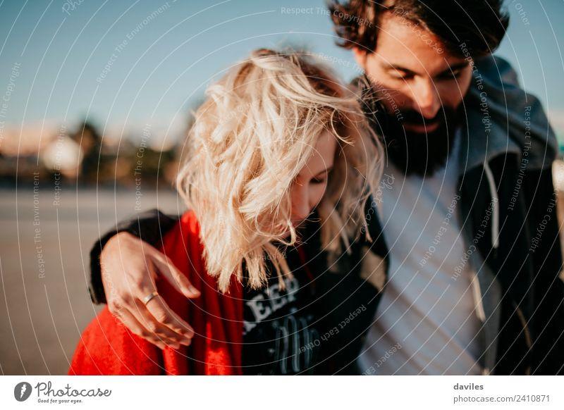 Blonde Frau und bärtiger Mann gehen zusammen im Freien spazieren. Lifestyle Freude Erwachsene Paar Mode blond Vollbart Lächeln Liebe Umarmen Coolness