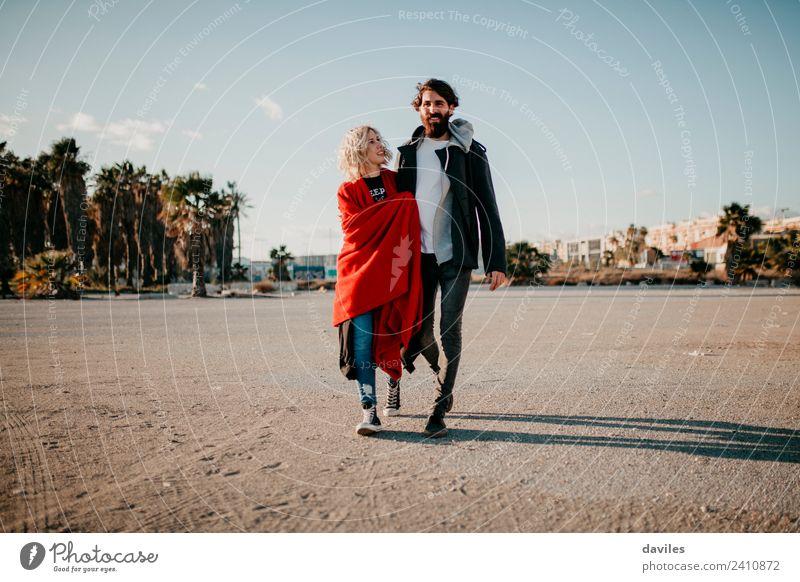 Blonde Frau und bärtiger Mann gehen bei Sonnenuntergang im Freien umarmt spazieren. Lifestyle Freude Winter Erwachsene Paar blond Vollbart Lächeln Liebe Umarmen
