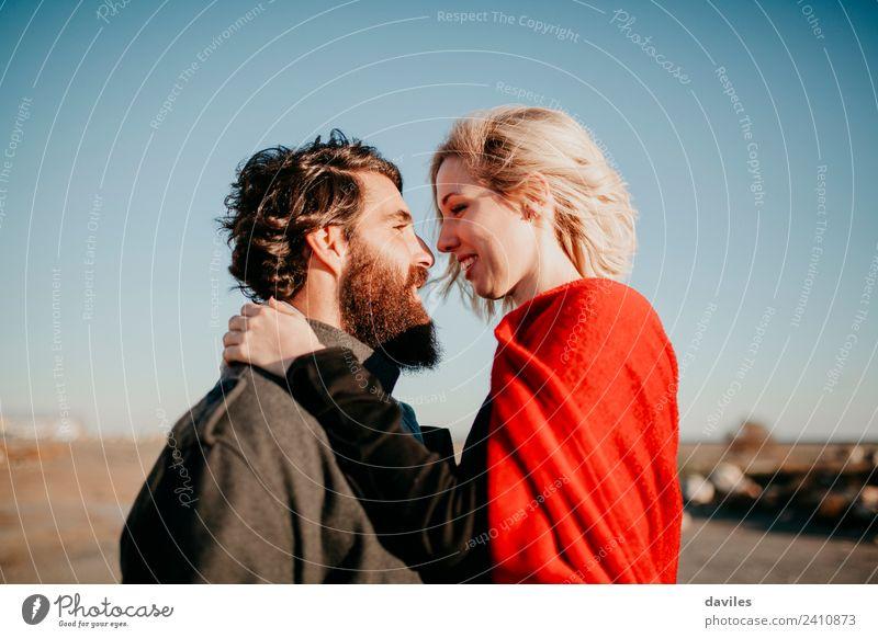 Bartiger Mann und blonde Frau schauen auf jeden. Lifestyle Freude Glück schön Sonne Winter Erwachsene Paar Mode Vollbart Küssen Lächeln Liebe Umarmen Coolness