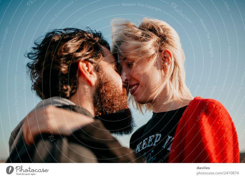 Blonde Frau und bärtiger Mann küssen Porträt mit wunderschönem Sonnenuntergangslicht. Lifestyle Freude Erwachsene Paar blond Vollbart Küssen Lächeln Liebe