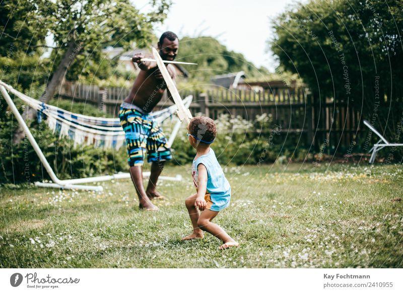 Vater spielt mit seinem Sohn im Garten Ritter Mensch Ferien & Urlaub & Reisen Mann Sommer Freude Erwachsene Lifestyle Leben Bewegung Familie & Verwandtschaft