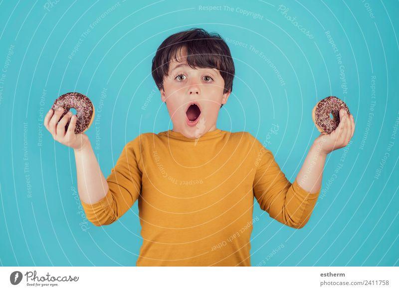 überraschter Junge mit Donuts in der Hand Lebensmittel Brötchen Süßwaren Schokolade Ernährung Frühstück Mittagessen Lifestyle Freude Mensch maskulin Kind