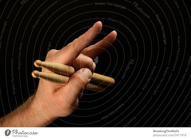 Mann Hand hält Trommelstöcke mit Teufelshörnern über Schwarz. Freizeit & Hobby Entertainment Musik Erwachsene Finger 1 Mensch Show Konzert Musiker Schlagzeug