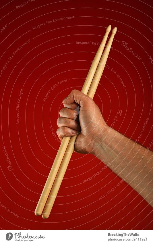 Mann Hand hält hölzerne Trommelstöcke über rotem Hintergrund. Musik Erwachsene 1 Mensch Bühne Show Konzert Musiker Holz Faust gestikulieren Rocker Schlagzeuger