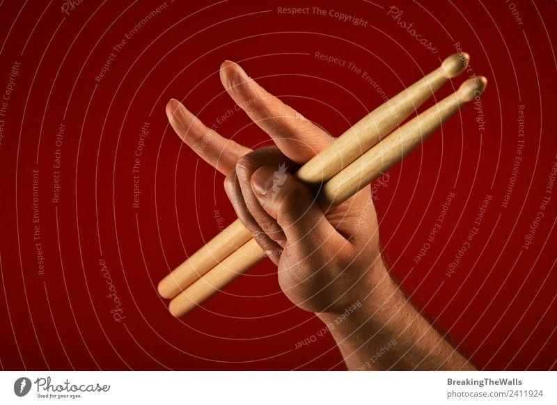 Männerhand mit Trommelstöcken und Teufelshörnern über rotem Hintergrund maskulin Mann Erwachsene Hand 1 Mensch Show Musik Konzert Bühne Musiker Schlagzeug