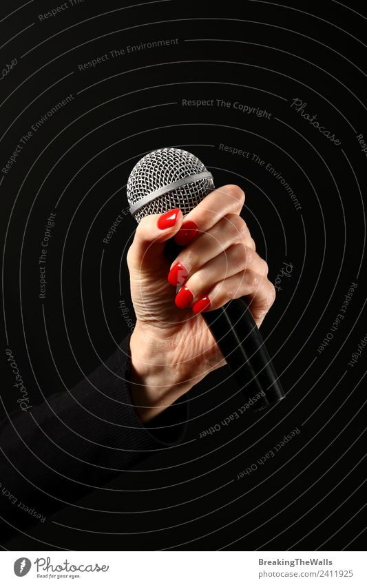 Damenhandmikrofon auf schwarzem Hintergrund Mensch Frau Erwachsene Hand 1 Schauspieler Show Musik Konzert Bühne Sänger Musiker Schallplatte Medien Fernsehen rot