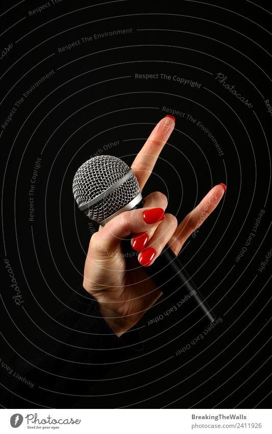 Damenhandmikrofon mit Teufelshörnern auf Schwarz feminin Junge Frau Jugendliche Erwachsene Hand Finger Punk Show Musik Konzert Bühne Sänger Musiker Medien rot