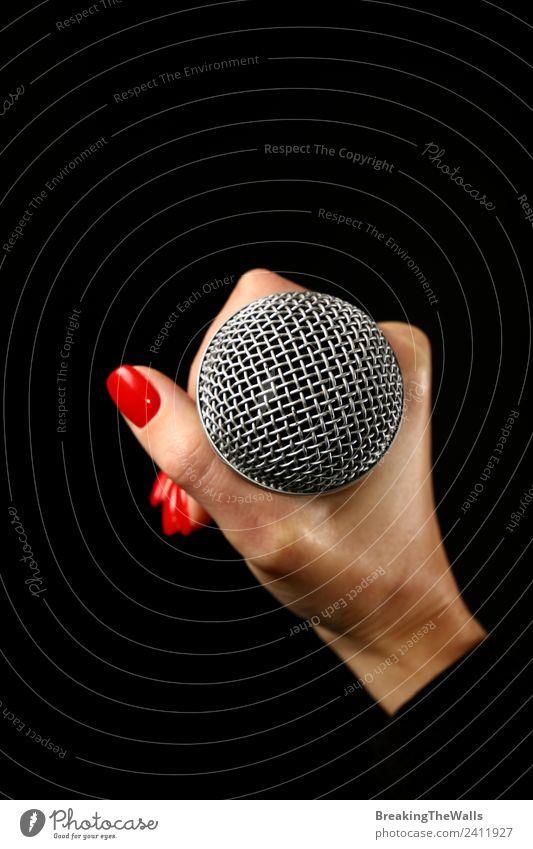 Damenhandmikrofon auf schwarzem Hintergrund Mensch Junge Frau Jugendliche Erwachsene Hand 1 Musik Konzert Bühne Sänger Musiker Schallplatte Medien Fernsehen rot