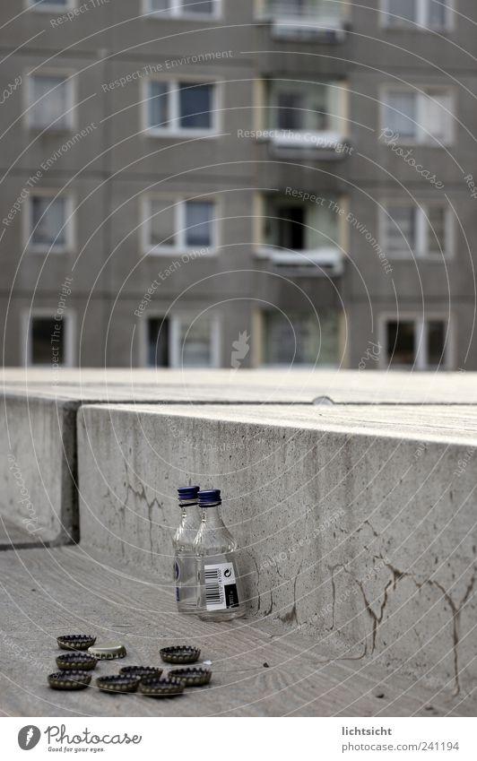 abwärts Alkohol Spirituosen trinken Stadt Hauptstadt Stadtrand Haus Hochhaus Platz Treppe Fassade Fenster Beton grau Verfall Verzweiflung schäbig Kronkorken