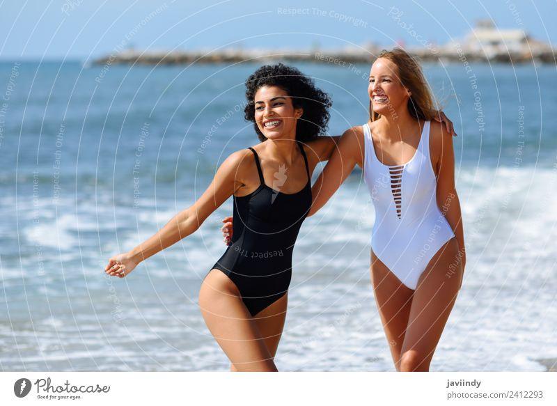 Zwei junge Frauen in Badebekleidung an einem tropischen Strand. Lifestyle Freude Glück schön Haare & Frisuren Freizeit & Hobby Ferien & Urlaub & Reisen