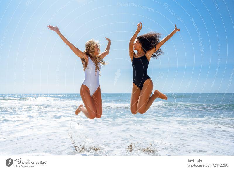 Zwei Frauen in Badebekleidung springen an einem tropischen Strand. Freude Ferien & Urlaub & Reisen Tourismus Sommer feminin Junge Frau Jugendliche Erwachsene