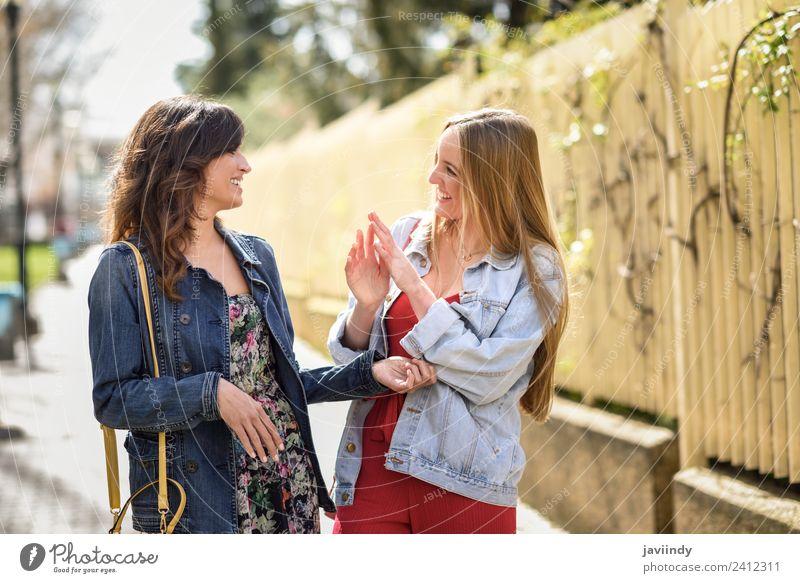 Zwei glückliche junge Frauen im Gespräch im urbanen Hintergrund Lifestyle Stil Freude Glück schön sprechen Mensch feminin Junge Frau Jugendliche Erwachsene