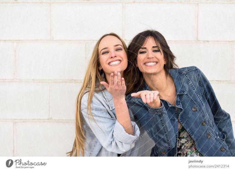 Zwei schöne Mädchen, die einen Kuss an der Stadtmauer im Freien blasen. Lifestyle Stil Freude Glück Mensch feminin Junge Frau Jugendliche Erwachsene