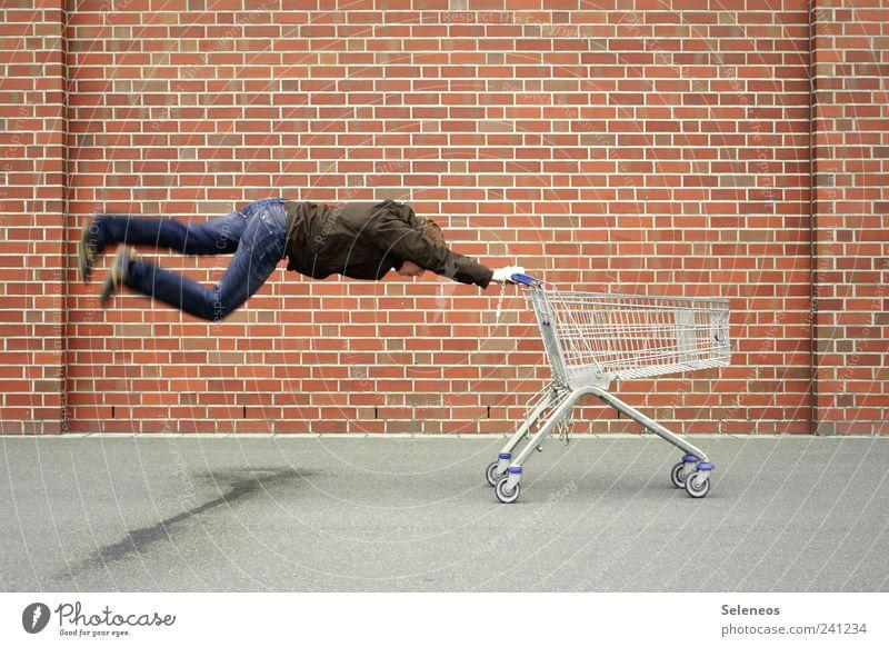 Shoppingwahn Industrie Handel Mensch maskulin Mann Erwachsene 1 Platz Mauer Wand Straße Jeanshose Backstein kaufen fliegen Geschwindigkeit verrückt Bewegung