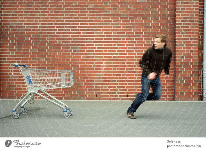 Shoppingtour Wirtschaft Handel Mensch maskulin Mann Erwachsene 1 Haus Mauer Wand Straße Jeanshose Jacke Einkaufswagen Backstein laufen stehen Geschwindigkeit