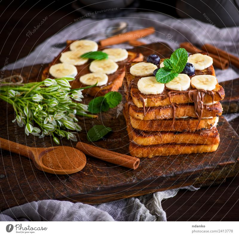 Französischer Toast auf das Frühstück Frucht Brot Dessert Ernährung Löffel Blume Holz frisch lecker oben Tradition Zuprosten Banane Schokolade Hintergrund