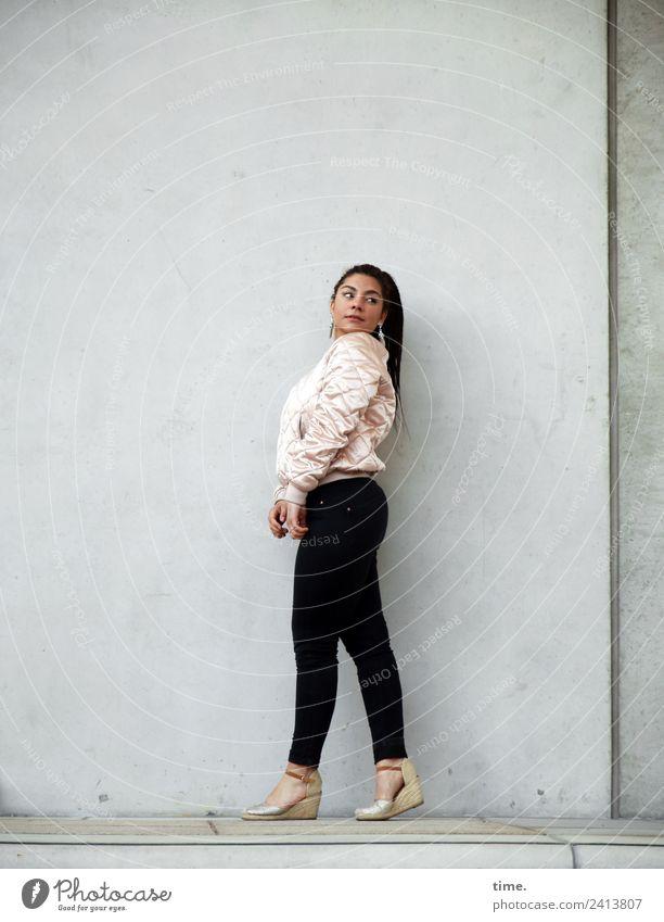 Nikolija feminin Frau Erwachsene 1 Mensch Mauer Wand Hose Jacke Damenschuhe brünett langhaarig Locken beobachten Denken gehen Blick stehen warten Neugier schön