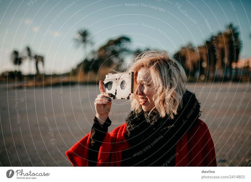 Blonde weiße Frau, die eine alte VHS-Kassette hält und damit spielt. Lifestyle Freude Freizeit & Hobby Mensch Junge Frau Jugendliche Erwachsene 1 18-30 Jahre