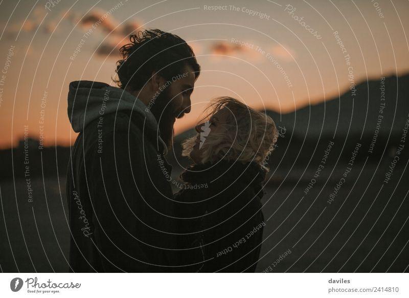 Blondes Mädchen und bärtiger Mann umarmen sich in der Abenddämmerung, mit orangefarbenem Himmel im Hintergrund. Lifestyle Freizeit & Hobby Tourismus Freiheit