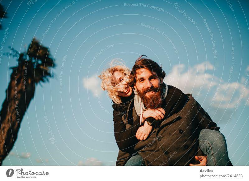 Bärtiger glücklicher Mann, der sie huckepack zu ihrer Freundin trägt, mit blauem Himmel im Hintergrund. Lifestyle Freude Freizeit & Hobby Spielen Mensch