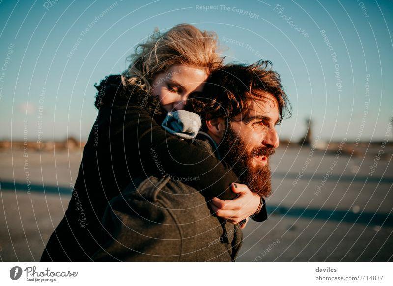 Bärtiger Mann, der seine Freundin bei Sonnenuntergang huckepack nach draußen trägt. Lifestyle Freude Freizeit & Hobby Mensch Junge Frau Jugendliche Junger Mann
