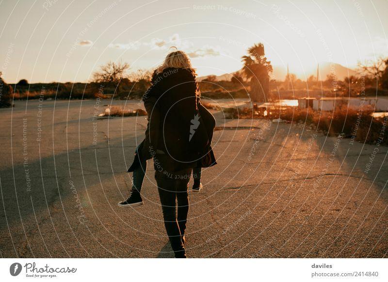 Mann, der bei Sonnenuntergang an einem verlassenen Ort huckepack zu seiner Freundin getragen wird. Lifestyle Spielen Mensch Junge Frau Jugendliche Junger Mann