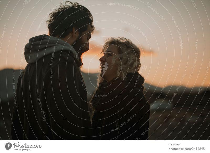 Blondes Mädchen lächelt und schaut in der Dämmerung zu ihrem Freund Lifestyle Freude Sonne Mensch Junge Frau Jugendliche Junger Mann Paar Partner 2 18-30 Jahre