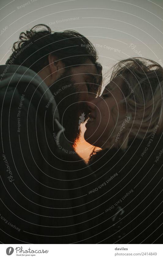 Bärtiger Mann und blonde Frau küssen sich unter freiem Himmel. Mensch Erwachsene Paar 2 18-30 Jahre Jugendliche Vollbart genießen Küssen Lächeln Liebe Umarmen