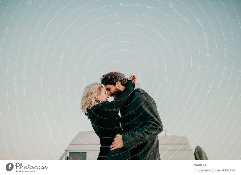 Blondes Mädchen und bärtiger Mann umarmen sich im Freien mit einem Lieferwagen im Hintergrund. Lifestyle Freude Ferien & Urlaub & Reisen Ausflug Camping