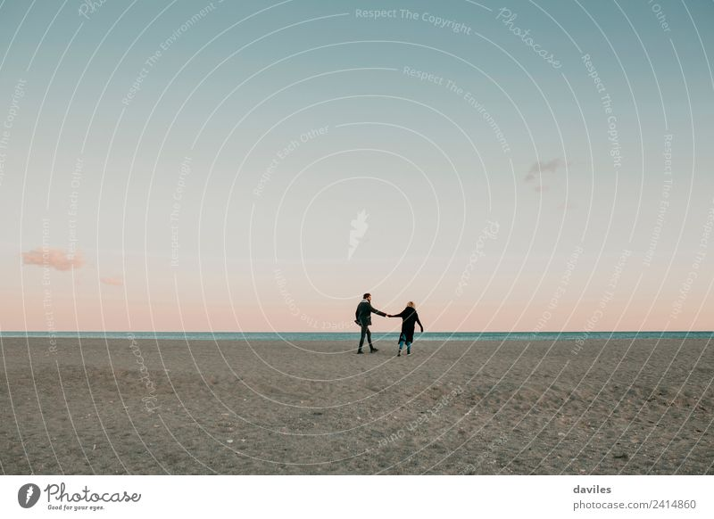 Junges Paar, das in der Abenddämmerung an einem einsamen Strand mit dem Meer im Hintergrund auf dem Sand spazieren geht. Lifestyle Winter Mensch Junge Frau