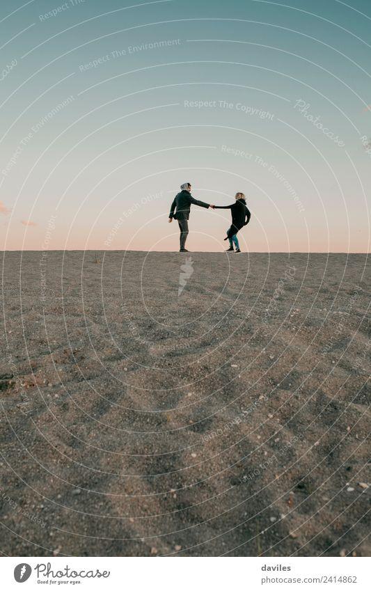 Liebliches Paar beim Spaziergang durch den Sand am Strandhorizont. Lifestyle Freude schön Winter Mensch Junge Frau Jugendliche Junger Mann Erwachsene Partner 2