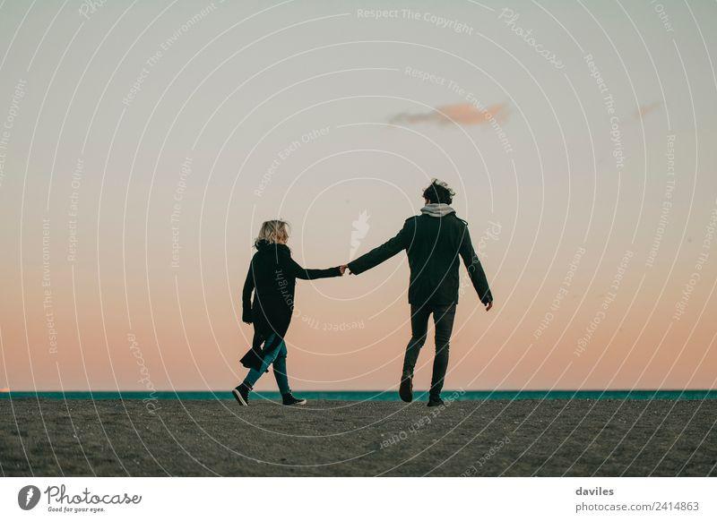 Junges Paar geht in der Abenddämmerung an der Hand auf dem Strandsand Lifestyle Freude schön Ferien & Urlaub & Reisen Meer Winter Mensch Frau Erwachsene Mann
