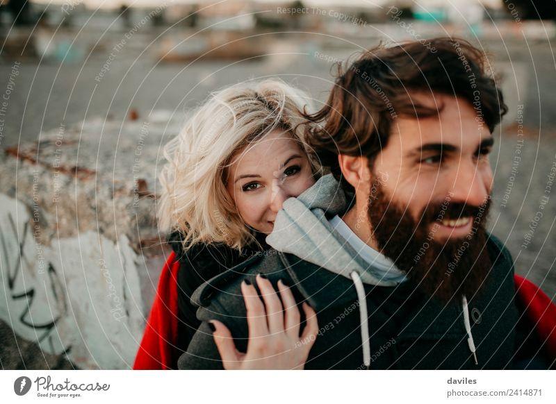 Blondes Mädchen schaut in die Kamera, während sie ihren bärtigen Freund umarmt. Lifestyle Freizeit & Hobby Mensch Junge Frau Jugendliche Junger Mann Erwachsene