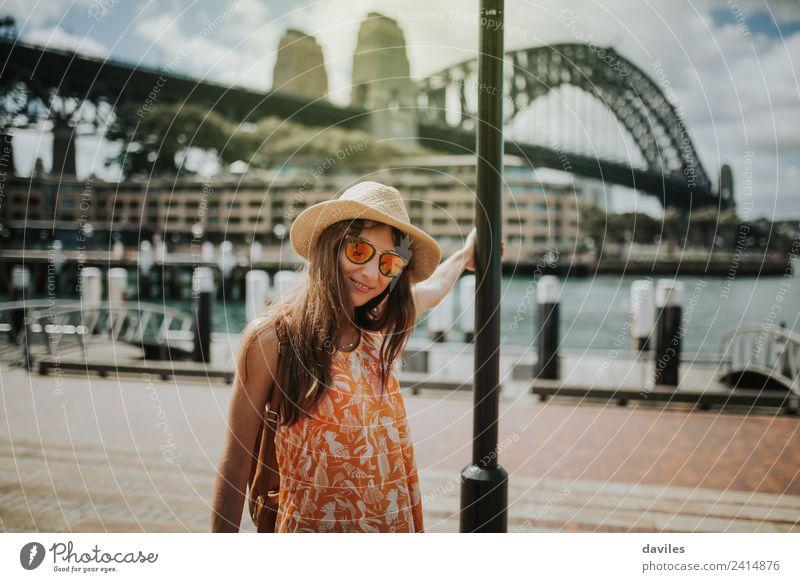 Süßes Mädchen mit Hut und Sonnenbrille posiert in der Stadt Sydney, mit der Harbour Bridge im Hintergrund, Australien. Lifestyle Ferien & Urlaub & Reisen