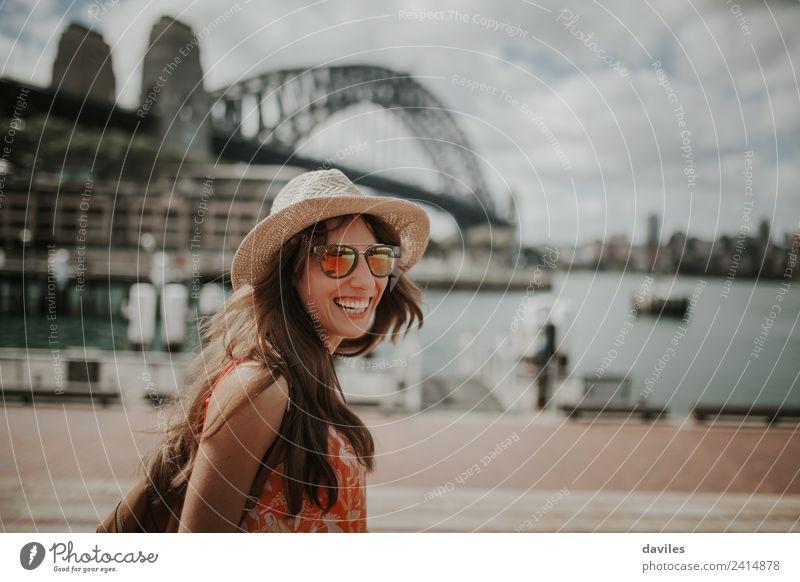 Glückliche blonde Frau mit Hut und Sonnenbrille lacht im Hafen der Stadt Sydney, mit der Harbour Bridge im Hintergrund, in Australien. Lifestyle Stil Freude