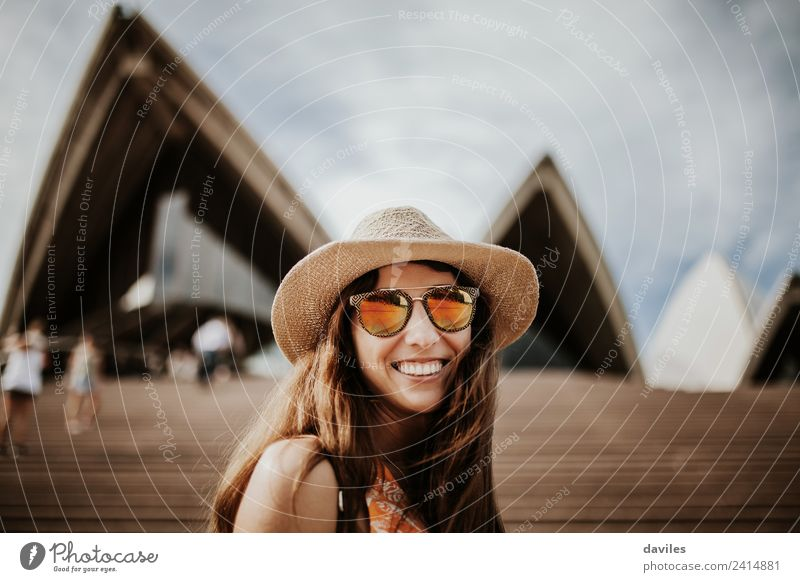 Reizende Frau mit Hut und Sonnenbrille, die in die Kamera schaut, während sie das Opernhaus in Sydney, Australien, besucht. Lifestyle Freude