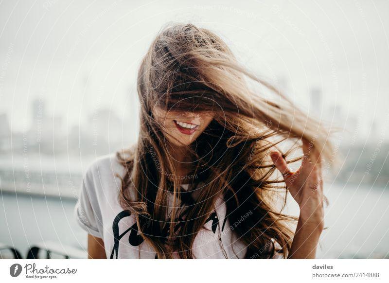 Blonde Frau, die ihr Haar an einem windigen Tag berührt. Lifestyle Freiheit Sommer Mensch Erwachsene Haare & Frisuren 1 18-30 Jahre Jugendliche Jugendkultur