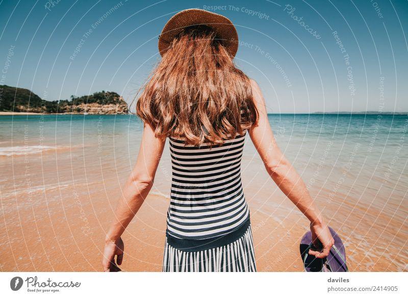 Eine Frau in ihrem Rücken, die in das Strandwasser geht. Lifestyle Wohlgefühl Ferien & Urlaub & Reisen Tourismus Abenteuer Sommer Meer Mensch Erwachsene 1