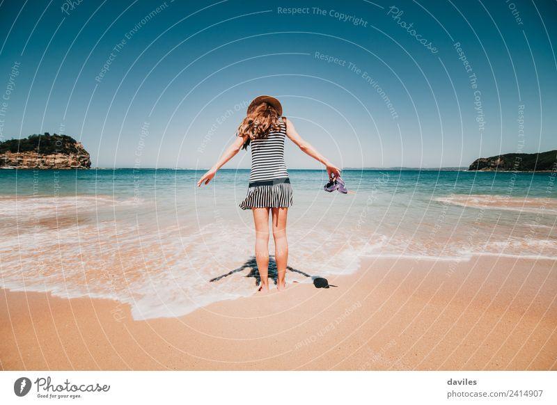 Frau mit einem Kleid und einem Hut, die in der Bucht von Maitland, NSW, Australien, ins Strandwasser geht. Lifestyle Ferien & Urlaub & Reisen Tourismus