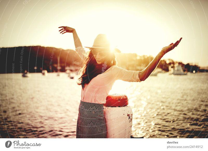 Lächelnde Frau mit Sonnenbrille und Hut, die die Arme hebt, glücklich mit dem Meer im Hintergrund. Lifestyle elegant Stil Wohlgefühl Ferien & Urlaub & Reisen