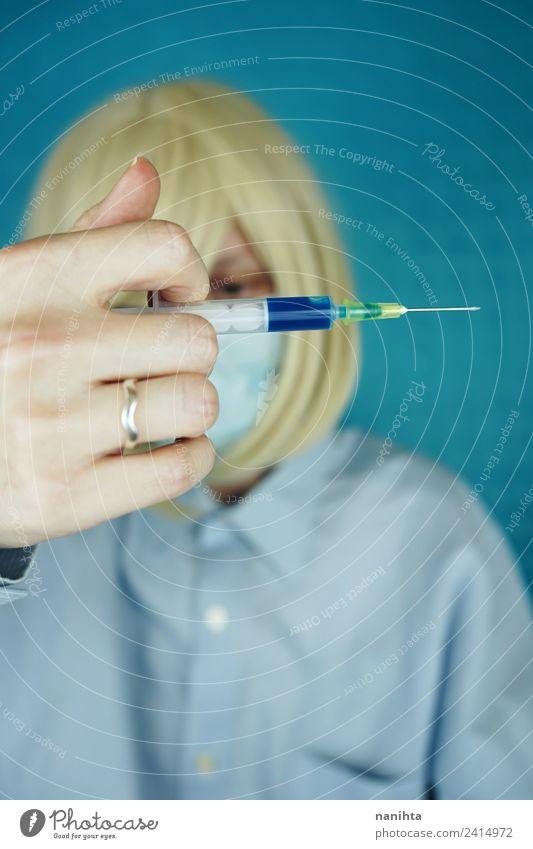 Junge Frau mit OP-Maske, die eine Spritze hält. Design Gesundheit Gesundheitswesen Behandlung Krankenpflege Krankheit Rauschmittel Medikament